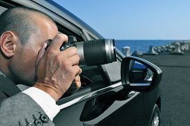 pic of investigation  - a detective or a paparazzi taking photos from inside a car - JPG