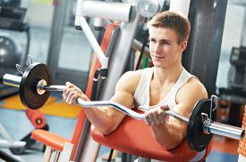 image of triceps brachii  - athlete man workout biceps brachii muscles exercises with training weight in fitness gym - JPG