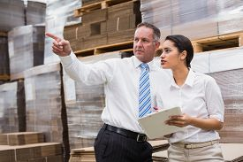foto of warehouse  - Warehouse manager and her boss checking inventory in a large warehouse - JPG