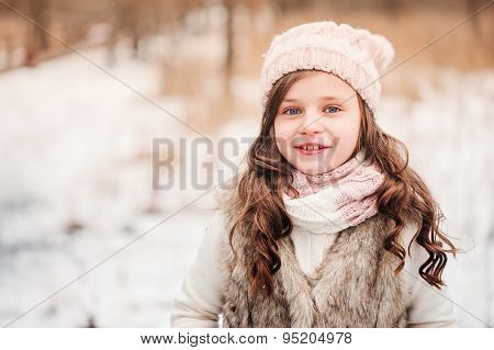 winter close up outdoor portrait of happy child girl in knitted hat and fur coat
