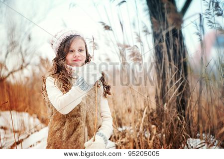 curly kid girl playing in winter snowy forest