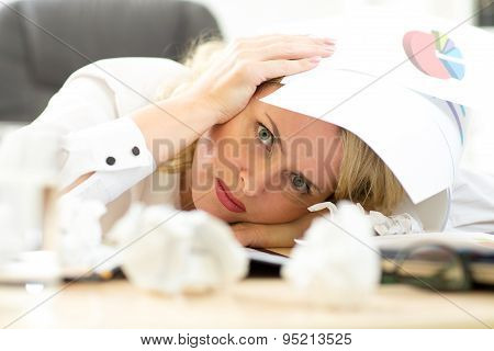 Tired Female Executive Filling Out Documents While Sitting At Her Desk