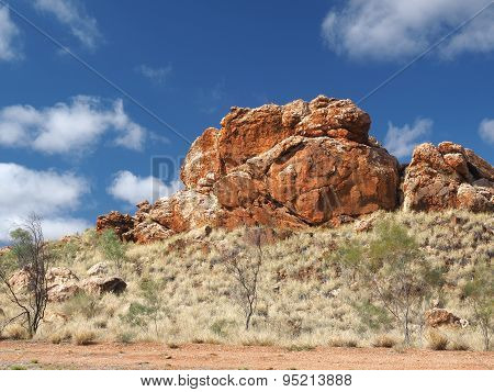 Deep red outback rock formation under blue sky
