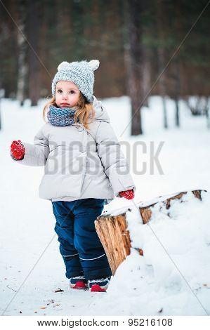 cute baby girl walking in winter snowy park
