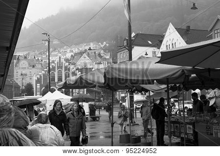 BERGEN, NORWAY - JUN 10 2015 : Shoppers attempt to stay dry at the famous Fish Market.