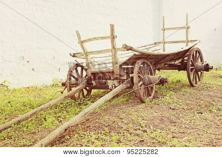 Vintage Old Rough Wooden Cart Near Old Clay Wall.
