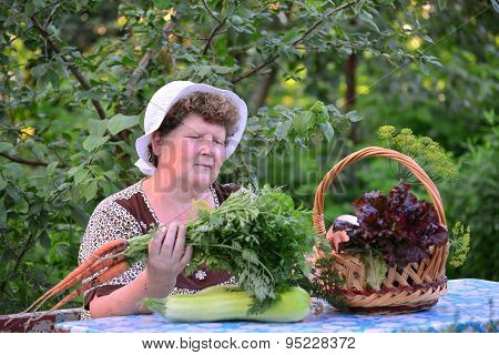 Elderly Woman With  Basket Of Vegetables Sitting At The Table