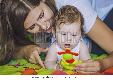 Woman With A Baby Play Colorful Toy In Front Of Them In Order To Develop And Attract Attention