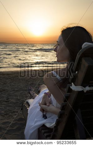 Woman Lying On Sun Lounger And Looking At Sunset