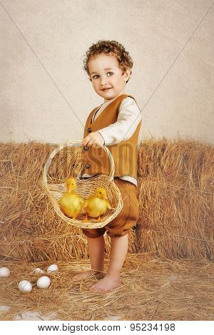 Beautiful Curly-haired Boy Holding Ducklings In A Basket
