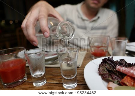 Man Pouring Vodka From A Carafe