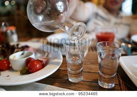 Person Fills Glasses Of Vodka