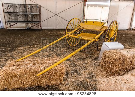 Yellow Empty Carriage Sits Near Hay Bales