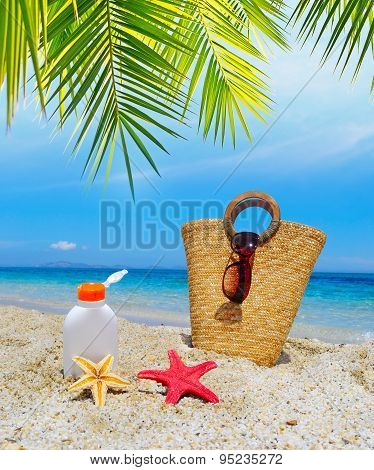 Straw Bag And Suntan Bottle Under A Palm Tree