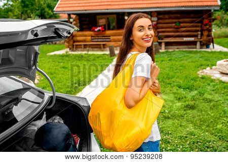Woman packing near the car with house on backgraound