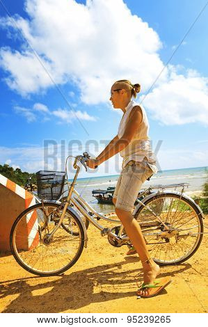 Young Woman Riding Bicycle Across River Bridge Next To Tropical Park
