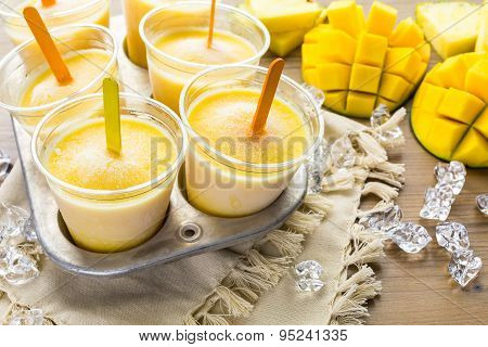 Homemade low calorie popsicles made with mango pineapple and coconut milk.