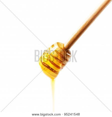 Wooden Honey Dipper With Yellow Honey Flowing Drops Isolated On White Background Macro.