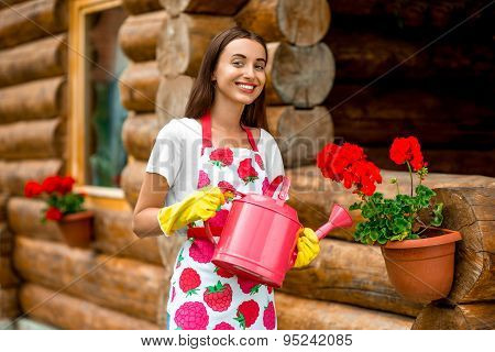 Woman watering flowers near the wooden cottage