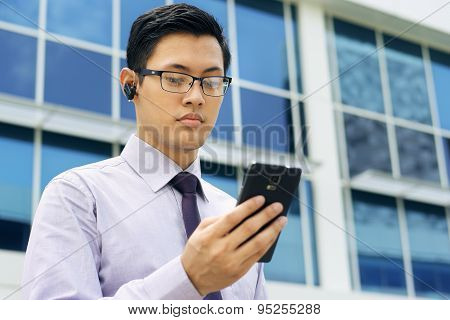 Businessman Talking Video Call On Mobile With Wireless Headset
