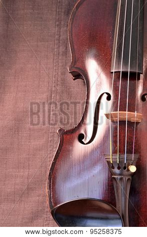 Antique Violin Closeup Against Gray Fabric Background Vertical