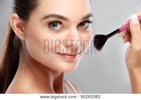 Attractive Model Smiling While Tidy Up Her Make Up