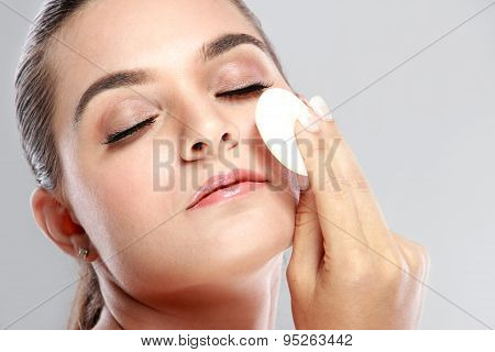 Beautiful Woman Applying Some Powder Using Powder Puff With Closed Eyes