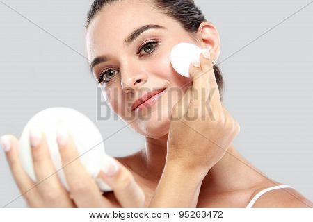 Cheerful Young Model Smiling While  Holding A Compact Powder And Applying Some Powder