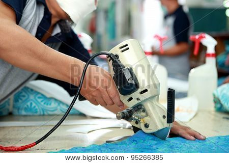 Worker Using Cutting Machine For Cutting Fabrics