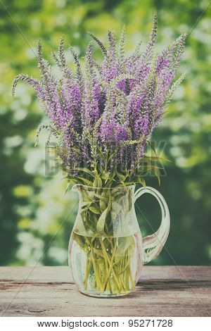 Bunch Of Wild Flowers In A Jug On Old Wooden Table. Vintage Stylized.