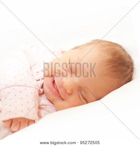 Smiling Newborn Baby Sleeping. Isolated On White