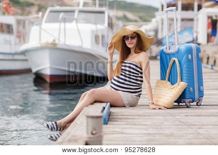 Pregnant beautiful woman on the pier at the sea