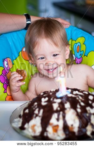 Baby boy blows out candles on a cake