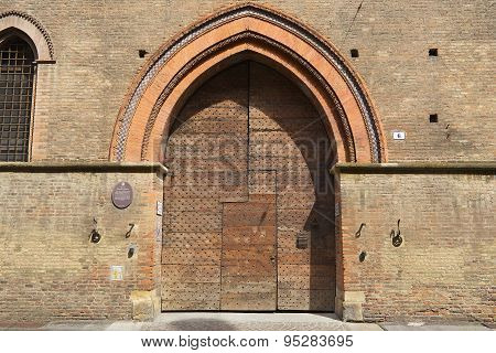 Exterior of the old wooden gate of Pepoli Vacchio palace in Bologna, Italy.