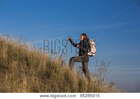 Female backpacker ascends steep hill