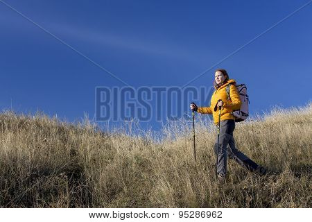 Female hiker walks downhill and enjoys warm sunlight