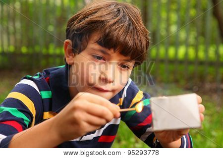 preteen handsome boy play with box of matches