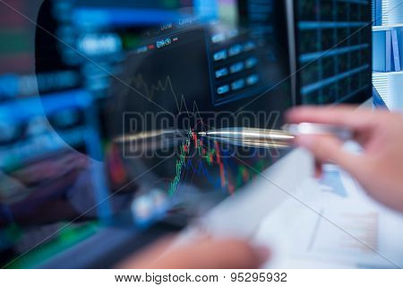 Touching stock market graph on a touch screen device. Trading on stock market concept. Closeup photo