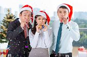 image of blowers  - Vietnamese coworkers with party blowers celebrating Christmas - JPG
