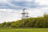 stock photo of power transmission lines  - power transmission lines against the sky and wood - JPG
