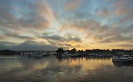 pic of glorious  - A Glorious Sunrise is Reflected in the Calm Waters of a Marina - JPG