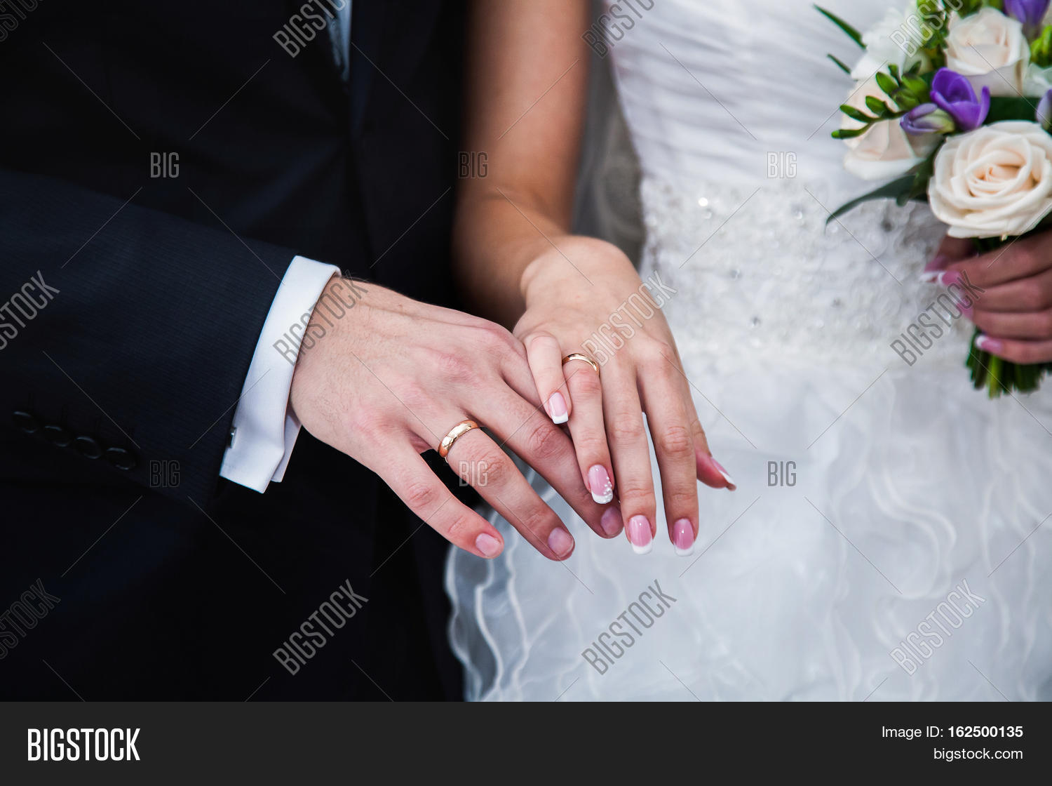 Bride And Groom Next To Wedding Rings On Their Hands Male And Female Hand With Wedding Rings