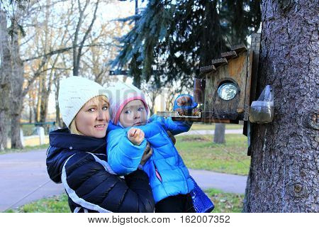 mother with her daughter feeds the birds in the feeding-rack in the Autumnal park