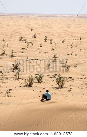 Man tourist in desert rub al khali in Oman sitting in sand view landscape 3