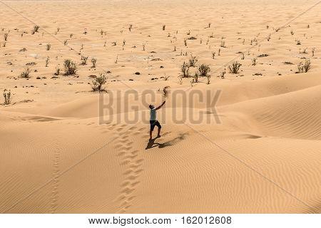 Man tourist in desert rub al khali in Oman throwing sand