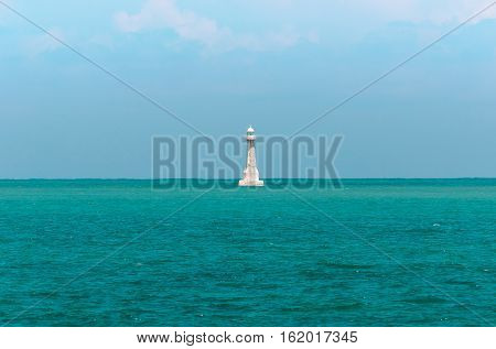 White lighthouse in the middle of the sea. Lighthouse surrounded by blue sea water and a blue sky background.
