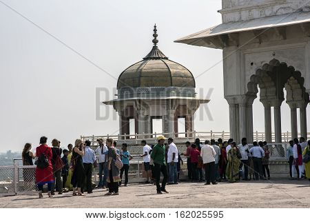 Agra, India - October 11, 2016: Tourists admiring and posing with Samman Burj (octagonal tower) and Shah Jahan's private hall Diwan-i-khas of ancient Agra Fort, Agra, India. Agra Fort is a Mughal Architectural Masterpiece.