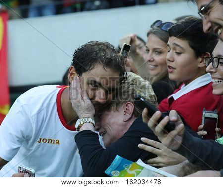 RIO DE JANEIRO, BRAZIL - AUGUST 12, 2016: Olympic champion Rafael Nadal of Spain with tennis fan after men's singles semifinal of the Rio 2016 Olympic Games at the Olympic Tennis Centre