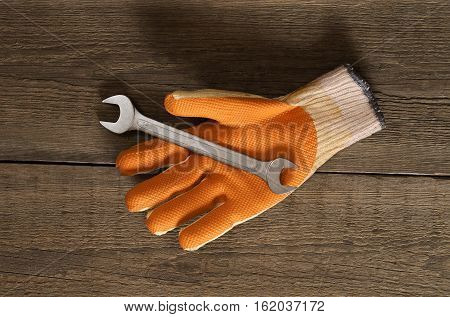 wrench lying on the working glove on a wooden background