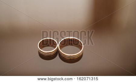 Golden wedding rings on mirror glasses table - one lies near another, macro, close up